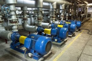 Four blue industrial pumps are aligned next to each other in an industrial warehouse.