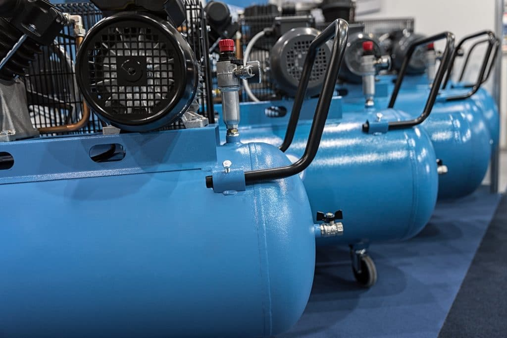 three electric air compressors lined up in a garage